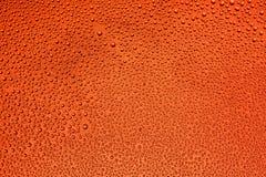 Πτώσεις του νερού στο γυαλί με ένα κόκκινο υπόβαθρο Στοκ φωτογραφία με δικαίωμα ελεύθερης χρήσης