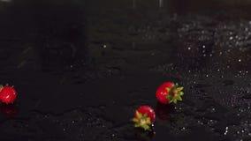 Πτώσεις φραουλών με το νερό σε έναν μαύρο πίνακα απόθεμα βίντεο