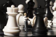 Πτώση βασιλιάδων Chessman και σκακιού στον πίνακα παιχνιδιών Σκάκι παιχνιδιού με τη μικροσκοπική μακρο φωτογραφία κουκλών Στοκ Φωτογραφίες