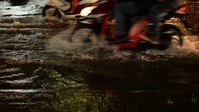 Πτώση βροχής οδών πλημμυρών τη νύχτα με τη μοτοσικλέτα και τα αυτοκίνητα ως υπόβαθρο απόθεμα βίντεο