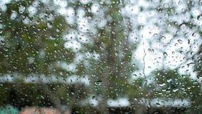 Πτώση βροχής στον εξωτερικό καθρέφτη με το θολωμένο υπόβαθρο φιλμ μικρού μήκους