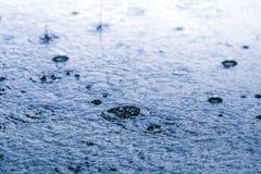 Πτώση βροχής στο έδαφος στην μπλε διάθεση Στοκ εικόνα με δικαίωμα ελεύθερης χρήσης