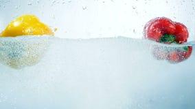 Πτώση δύο γλυκών πιπεριών στο νερό από κοινού απόθεμα βίντεο