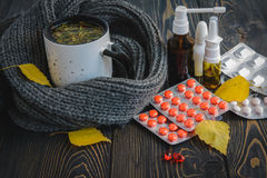 Πτώση και υγειονομική περίθαλψη Κρύο - φλυτζάνι του τσαγιού, θερμόμετρο χαπιών σε ένα ξύλινο υπόβαθρο στοκ φωτογραφία