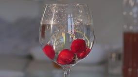 Πτώση κερασιών σε ένα γυαλί με το νερό απόθεμα βίντεο