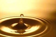 Πτώση νερού - καθαροί σαφής και διαφανής του νερού και του κυματισμού στο χρυσό υπόβαθρο Στοκ Φωτογραφίες