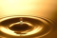 Πτώση νερού - καθαροί σαφής και διαφανής του νερού και του κυματισμού στο χρυσό υπόβαθρο Στοκ Εικόνα