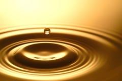 Πτώση νερού - καθαροί σαφής και διαφανής του νερού και του κυματισμού στο χρυσό υπόβαθρο Στοκ Εικόνες