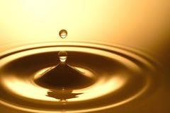 Πτώση νερού - καθαροί σαφής και διαφανής του νερού και του κυματισμού στο χρυσό υπόβαθρο Στοκ εικόνα με δικαίωμα ελεύθερης χρήσης