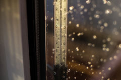 Πτώση στη θερμοκρασία σε μια κλίμακα θερμομέτρων Πτώσεις της βροχής στο παράθυρο μετά από μια θύελλα στοκ εικόνα με δικαίωμα ελεύθερης χρήσης