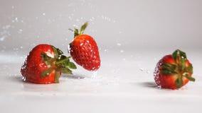 Πτώση φραουλών στην άσπρη υγρή επιφάνεια φιλμ μικρού μήκους