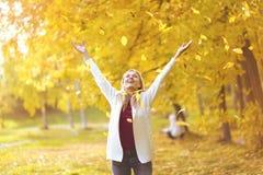 Πτώση φύλλων, ευτυχής γυναίκα στο πάρκο φθινοπώρου Στοκ Εικόνα