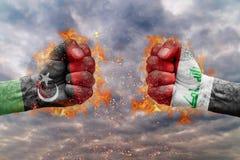 Πυγμή δύο με τη σημαία της Λιβύης και του Ιράκ που απασχολούνται ο ένας στον άλλο Στοκ Εικόνες