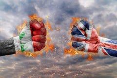 Πυγμή δύο με τη σημαία του Ιράκ και της Μεγάλης Βρετανίας που απασχολούνται ο ένας στον άλλο Στοκ Εικόνες