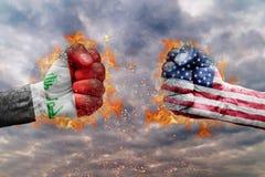 Πυγμή δύο με τη σημαία του Ιράκ και των ΗΠΑ που απασχολούνται ο ένας στον άλλο Στοκ εικόνα με δικαίωμα ελεύθερης χρήσης