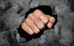 Πυγμή που σπάζει τον παλαιό βρώμικο συμπαγή τοίχο Στοκ φωτογραφία με δικαίωμα ελεύθερης χρήσης