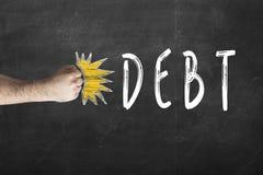 Πυγμή που χτυπά το χρέος που γράφεται στον πίνακα κιμωλίας στοκ φωτογραφία