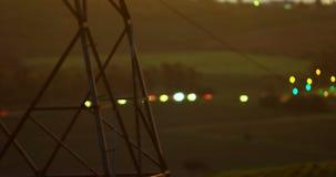Πυλώνας ηλεκτρικής ενέργειας ενάντια στα φω'τα 4K 4k οχημάτων bokeh απόθεμα βίντεο