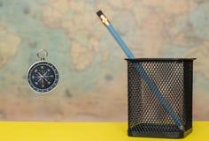 Πυξίδα και μολύβι σε ένα δοχείο μετάλλων σε ένα θολωμένο υπόβαθρο ενός χάρτη Παλαιών Κόσμων στοκ εικόνα με δικαίωμα ελεύθερης χρήσης