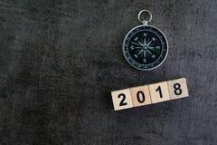 Πυξίδα και ξύλινος αριθμός φραγμών 2018 στο σκοτεινό μαύρο υπόβαθρο όπως Στοκ Εικόνες