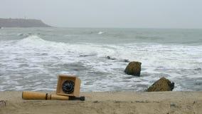 Πυξίδα και τηλεσκόπιο τηλεσκοπίων στην άμμο Βυθισμένη φορτηγίδα, στυλίσκος και bitt απόθεμα βίντεο