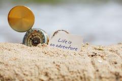 Πυξίδα στην άμμο με το μήνυμα - η ζωή είναι μια περιπέτεια στοκ φωτογραφία