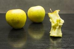 Πυρήνας της Apple και δύο μήλα σε έναν σκοτεινό ξύλινο πίνακα Στοκ φωτογραφία με δικαίωμα ελεύθερης χρήσης