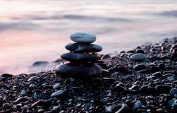 Πυραμίδα πετρών στην παραλία χαλικιών στο ηλιοβασίλεμα Στοκ φωτογραφία με δικαίωμα ελεύθερης χρήσης