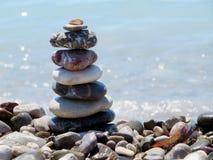 Πυραμίδα των μεγάλων χαλικιών με το κοχύλι στην κορυφή στην παραλία Η θάλασσα είναι το υπόβαθρο, ηλιόλουστη ημέρα Στοκ εικόνα με δικαίωμα ελεύθερης χρήσης