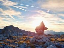 Πυραμίδα χαλικιών Πέτρες στην αλπική κορυφή βουνών αμμοχάλικου Ορίζοντας χαραυγών επάνω από την μπλε ομιχλώδη κοιλάδα Στοκ Εικόνες
