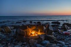 Πυρκαγιά θαλασσίως με το ηλιοβασίλεμα Καταπληκτική θέση για τη χαλάρωση και την αρμονία Στοκ Εικόνα