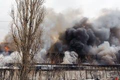 Πυρκαγιά και μαύρος καπνός πέρα από το κάψιμο του εργοστασίου Στοκ Εικόνα