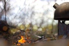 Πυρκαγιά και teapot στο ξύλο Στοκ Φωτογραφία