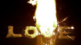 Πυρκαγιά που καίει επάνω την αγάπη λέξης στη μαύρη επιφάνεια απόθεμα βίντεο