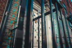Πυροβοληθείς από κάτω από μιας πύλης σιδήρου μπροστά από μια πόρτα στοκ εικόνα με δικαίωμα ελεύθερης χρήσης