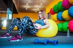 Πυροβοληθείς της νέας άσκησης γυναικών στη γυμναστική Μυϊκό θηλυκό που εκπαιδεύει χρησιμοποιώντας μια σφαίρα να κάνει κάθεται τη  Στοκ εικόνα με δικαίωμα ελεύθερης χρήσης