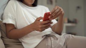 Πυροβοληθείς το των χεριών γυναικών ` s που κρατούν ένα smartphone καθμένος σε ένα οικογενειακό περιβάλλον φιλμ μικρού μήκους