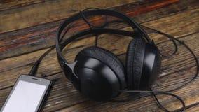 Πυροβοληθε'ν ολισθαίνων ρυθμιστής smartphone με τα ακουστικά στον παλαιό ξύλινο πίνακα απόθεμα βίντεο