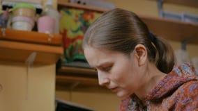 2 πυροβολισμοί Επαγγελματικός αγγειοπλάστης γυναικών που χρωματίζει τον κεραμικό συριγμό πενών αναμνηστικών στο εργαστήριο αγγειο απόθεμα βίντεο