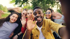 Πυροβολισμός άποψης των εύθυμων σπουδαστών που κάνουν τη σε απευθείας σύνδεση τηλεοπτική κλήση που καλεί τους φίλους που κρατούν  στοκ φωτογραφία με δικαίωμα ελεύθερης χρήσης