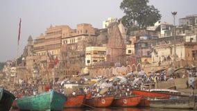 Πυροβολισμός βράσης των ζωηρόχρωμων βαρκών που δένονται από ένα ghat φιλμ μικρού μήκους