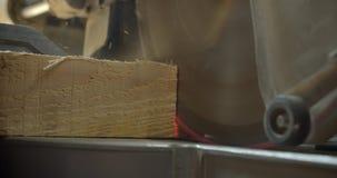 Πυροβολισμός κινηματογραφήσεων σε πρώτο πλάνο ενός κομματιού του κοπής του ξύλου με ένα ηλεκτρικό κομμένο πριόνι στην κατασκευή φιλμ μικρού μήκους
