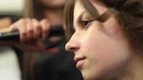 Πυροβολισμός κινηματογραφήσεων σε πρώτο πλάνο μιας γυναίκας που έχει την τρίχα της ισιωμένη στο κομμωτήριο Κατσαρώνοντας σίδηρος  απόθεμα βίντεο