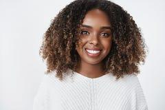 Πυροβολισμός κινηματογραφήσεων σε πρώτο πλάνο της χαλαρωμένης και χαρούμενης νέας γυναίκας σπουδαστή αφροαμερικάνων στο πουλόβερ  στοκ φωτογραφία με δικαίωμα ελεύθερης χρήσης
