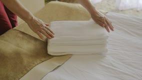 Πυροβολισμός κινηματογραφήσεων σε πρώτο πλάνο, το χέρια γυναικών ` s, επαγγελματικά που βάζει δύο φρέσκες καθαρές πετσέτες σε ένα απόθεμα βίντεο