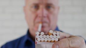Πυροβολισμός με το άτομο που προσφέρει σε ένα άλλο πρόσωπο ένα τσιγάρο από ένα πακέτο απόθεμα βίντεο