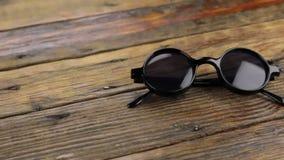 πυροβολισμός ολισθαινόντων ρυθμιστών Γυαλιά ηλίου κινηματογραφήσεων σε πρώτο πλάνο στον ξύλινο πίνακα φιλμ μικρού μήκους