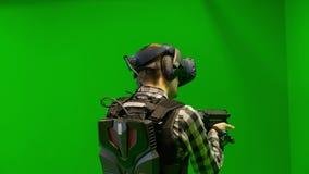 Πυροβολισμός παιχνιδιού τύπων στην εικονική πραγματικότητα σε ένα πράσινο υπόβαθρο VR παιχνίδι σκοπευτών με τη δοκιμή κασκών εικο φιλμ μικρού μήκους