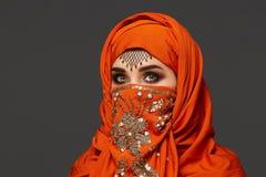 Πυροβολισμός στούντιο μιας νέας γοητευτικής γυναίκας που φορά την τερακότα hijab που διακοσμείται με τα τσέκια και το κόσμημα Αρα στοκ εικόνα