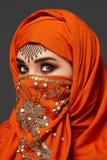 Πυροβολισμός στούντιο μιας νέας γοητευτικής γυναίκας που φορά την τερακότα hijab που διακοσμείται με τα τσέκια και το κόσμημα Αρα στοκ εικόνα με δικαίωμα ελεύθερης χρήσης